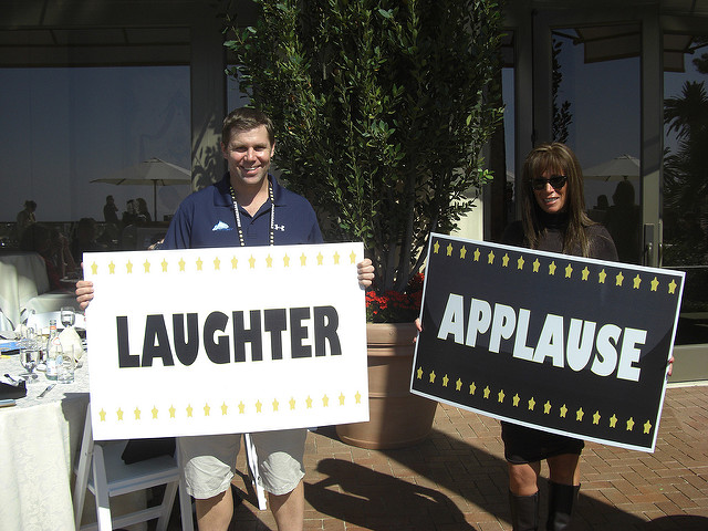 A man and a woman hold up giant cards saying Applauce and Laughter at a convention