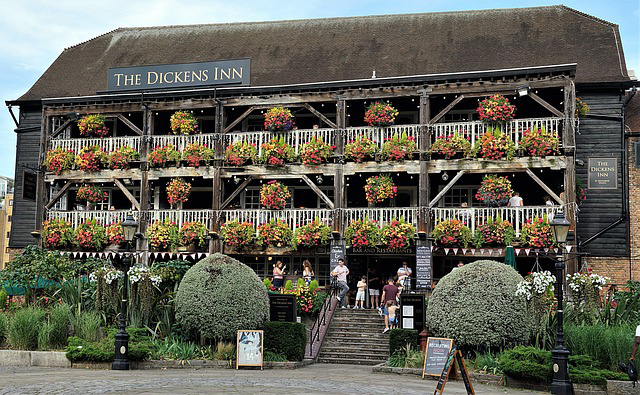 Three-story Dickens Inn festooned with hanging baskets of flowers on every level